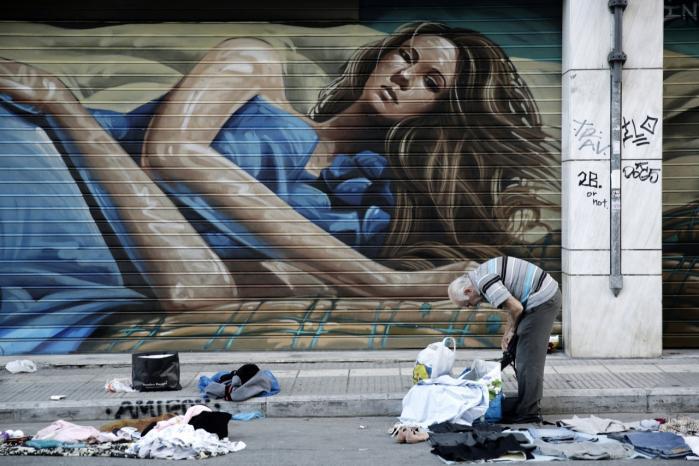 En gadesælger er ved at samle sit tøj sammen på en gade i Athen. Syv ud af ti grækere mener, at regeringen bør indgå et kompromis med EU, men dødvandet har fået de nervøse borgere til at hæve deres penge i bankerne. Mindst 30 mia. euro har grækerne hentet hjem til madrasserne siden årsskiftet