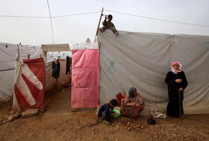 Syriske flygtninge udenfor deres telt i en flygtningelejr i den libaneniske byAl-Faour nær grænsen mellem Syrien og Libanon.