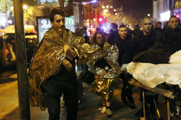 Ofre fra koncertstedet Bataclan går eller rulles væk på bårer fredag aften, efter at politi og sikkerhedsstyrker havde stormet stedet og dræbt de to personer, som med halvautomatiske våben dræbte omkring 100 personer.