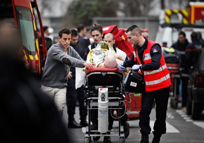 En såret person bliver kørt væk efter at brødrene Kouachi for et år siden trængte ind på Charlie Hebdo i Paris og dræbte 12 mennesker