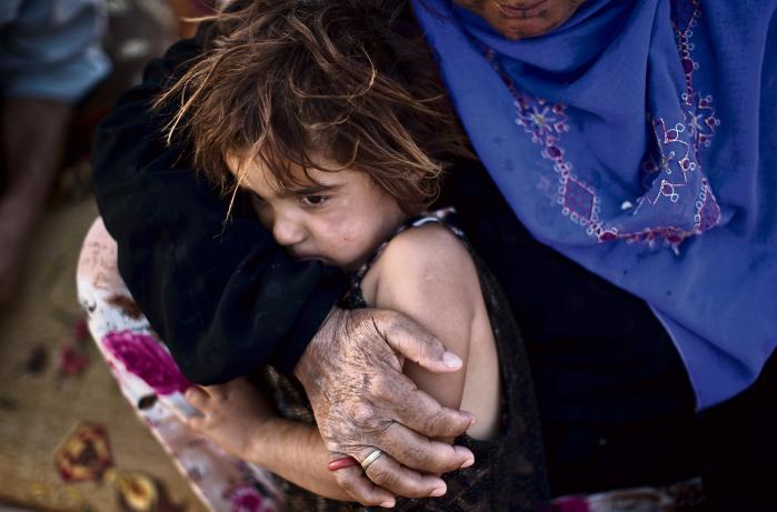 En ældre syrisk flygtninge ved navn Halima Ali giver sit barnebarn Amal et kram, mens de sidder i flygtningelejr i Jordan sidste år.