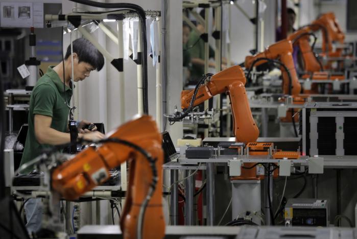 En mand arbejder mellem robotarme på Rapoo Technology-fabrikken i den sydlige kinesiske industriby Shenzhen. Verden over er robotter ved at overtage manuelt arbejde fra mennesker. Men frem for at begræde tabet af arbejde bør vi hylde robotterne for deres evne til at frigøre os fra arbejde, mener forfatteren Nick Srnicek.   Arkiv