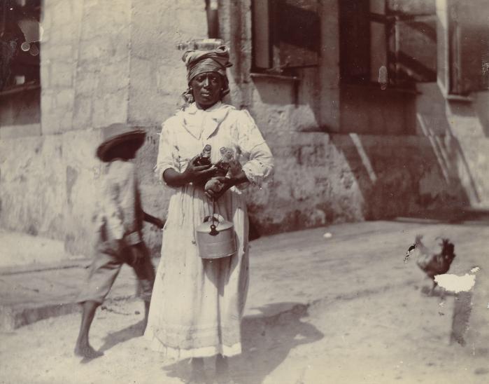 Kvinde bærende vandflasker og en gryde/beholder til vand fotograferet ved Centralfaktoriets Saftstation, Skt. Croix, 1903. En dreng og en høne går bag hende.