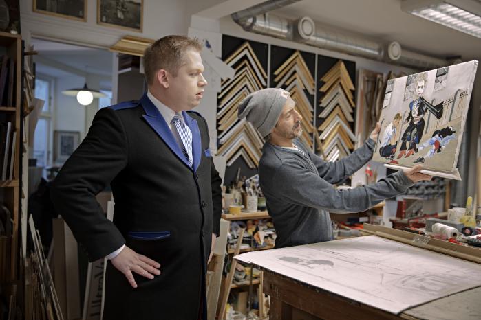 Uwe Max Jensen har malet to malerier til Rasmus Paludan. Det ene forestiller Lars Hedegaard og hænger på Paludans kontor. Det andet, som her er ved at blive indrammet, forestiller Paludan selv, der beskytter en skræmt politimand mod en terrorist.