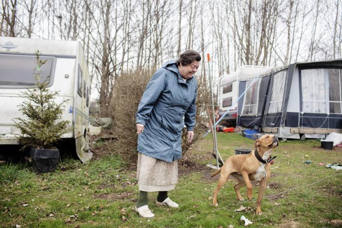 52-årige Margit Josiassen foran sin campingvogn med naboens hund, Chili. Margit bor på Borrevejle Camping på femte år og kunne ikke drømme om at flytte derfra. Hun holder meget af naboens børn, og hendes kærlighed til dyr gør, at hun prioriterer at købe økologiske varer, når hun har råd.