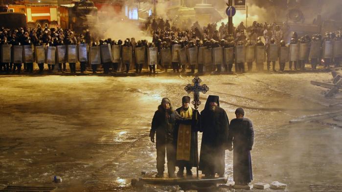 Religion og politik. Ortdokse præster i ingenmandslandet mellem polititropper og demonstranter under det ukrainske oprør. Kirkens engagement handler ikke kun om religion, men også om Ukraines historiske rolle som kastebold mellem fremmede magter.