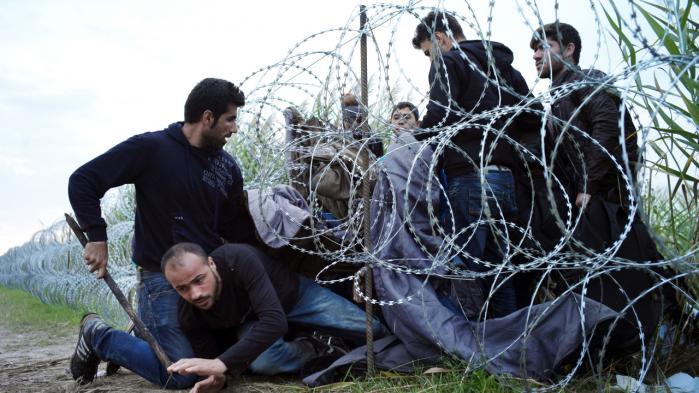 Syriske flygtninge maver sig under grænsepigtråden ind i Ungarn fra Serbien ved Röszke. Et fire meter højt grænsehegn er blev bygget, idet flere end 140.000 migranter er kommet til Ungarn i år. 80 pct. af dem kommer fra krigszoner som Syrien, Irak og Afghanistan.