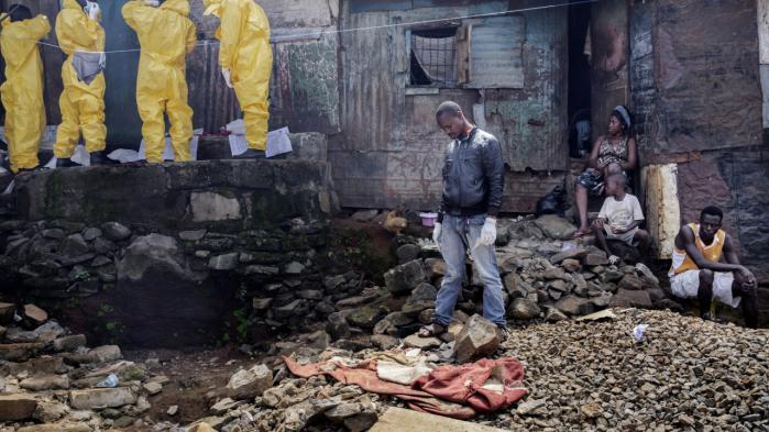 Et hold samler døde og sårede ebola-patienter ind i Freetown, Sierra Leone, 2014. Erfaringerne med en blanding af militært og civilt samarbejde var en begrænset succes, men ingen af organisationerne, der var involverede, vil afvise at lave et lignende samarbejde i fremtiden.