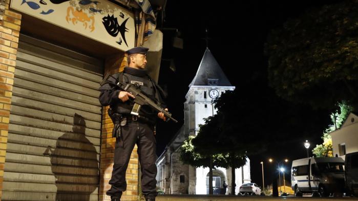 En politibetjent vogter foran kirken i  Saint-Etienne-du-Rouvray, hvor en katolsk præst tirsdag blev myrdet af to terrorister.