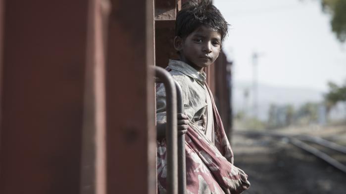 Lille Saroo (Sunny Pawar) ombord på det tog, der fører ham væk fra hans familie i Garth Davis' 'Lion'. Foto: Scanbox