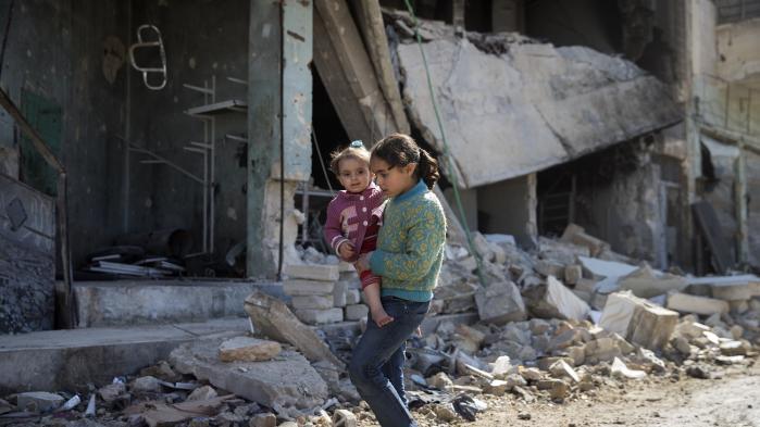 Syriske børn går gennem den ødelagte by Aleppo i begyndelsen af marts måned i år.