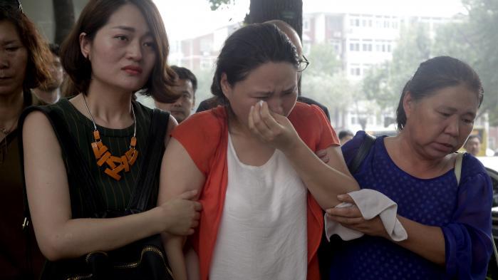 Li Wenzu (tv.), kone til den frihedsberøvede menneskerettighedsadvokat Wang Quanzhang, forlader en protest foran retten i Tianjin i Kina.