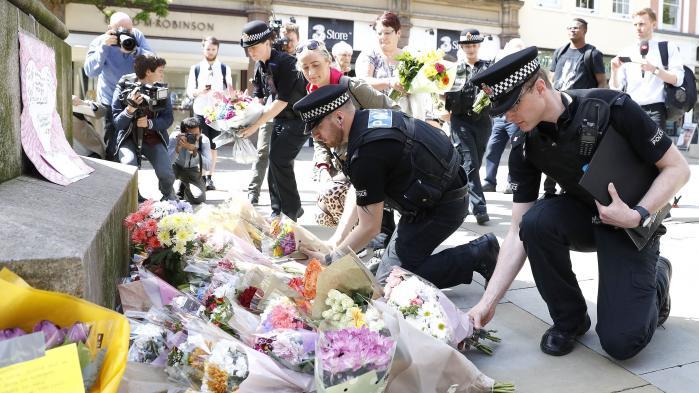 Betjente lægger blomster på St Ann's Square i Manchester efter angrebet mandag aften mod unge koncertdeltagere.