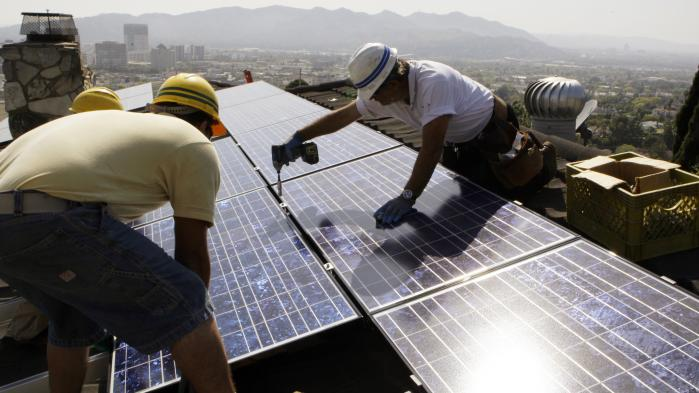 Installatører fra California Green Design installerer solpaneler på et tag i Glendale, Californien. USA's største delstat satser på en meget ambitiøs omstilling til grøn energi.