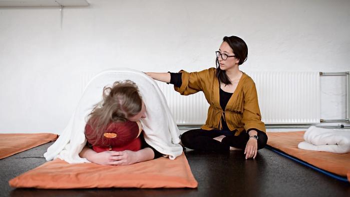 Mia Sung Kjærgaard underviser en stressramt i yoga. Der er altid kun en enkelt til stede ad gangen, bortset fra til den frivillige morgenyoga.