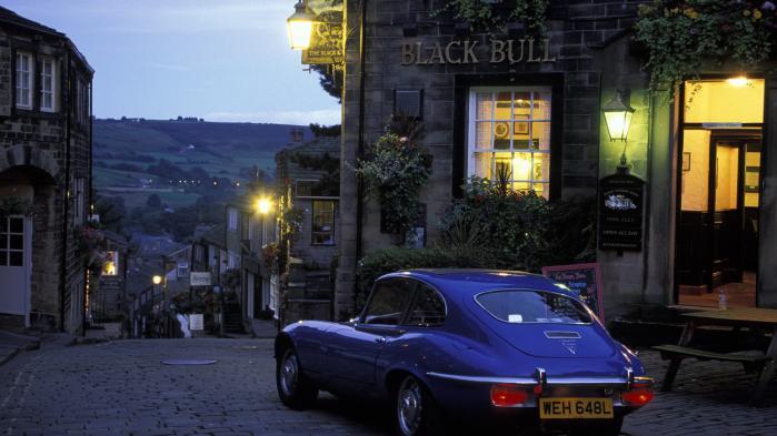 Jaguar E-type holder foran en pub iHaworth, Yorkshire.