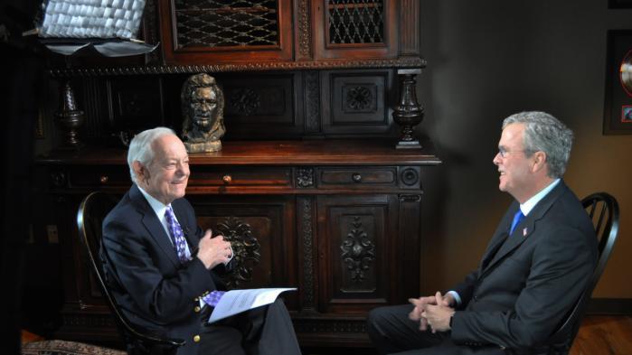 Penge spiller i dag en alt for stor rolle i USA's præsidentvalg, mener Bob Schieffer (t.v.), der her interviewer den republikanske præsidentkandidat Jeb Bush. Arkiv
