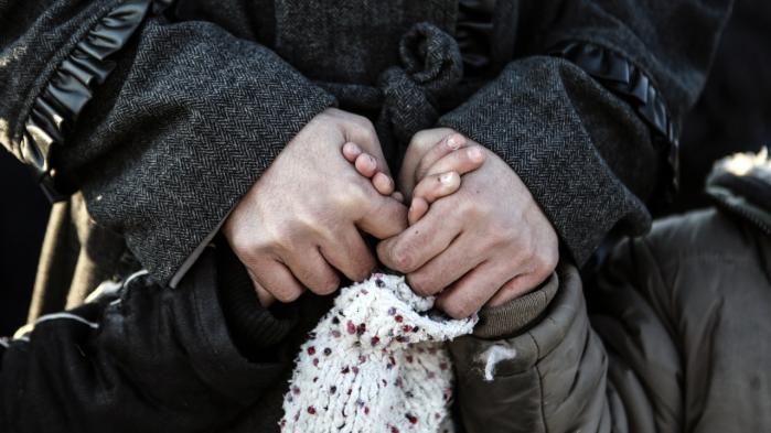 En flygtning holder to børn i hænderne i den tyrkiske by Didymoteicho tæt på den græske grænse. Europæiske politikere taler mere og mere om traffickere som ansvarlige for tragedierne på Europas grænser, men er det trafficking, når rejsen er selvvalgt?