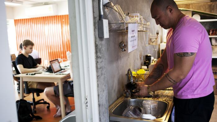 Johnny F.D. vasker sin AeroPress under halvtaget i Punspaces køkken. Indenfor sidder 20-30 unge mennesker og arbejder på deres computere.