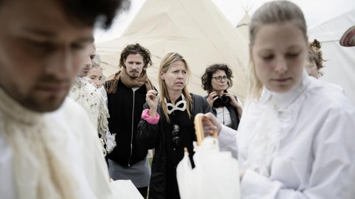 Mette Martinussen (i sort) befinder sig hele tiden i periferien, hvor hun styrer forestillingen med få bemærkninger og lavmælt gestik.
