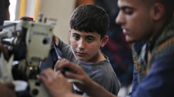 En 10-årig syrisk flygtning fra Aleppo arbejder med andre syrere i en tøjfabrik i Gaziantep i det sydøstlige Tyrkiet. Kun 30 procent af landets syriske flygtningebørn går i skole.