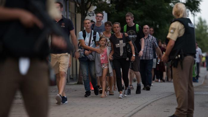 Fire dødelige angreb på en uge begået af personer af udenlandsk herkomst i Tyskland er blevet et politisk varmt emne. Her eksorterer politiet folk i sikkerhed efter fredagens attentat med 10 dræbte ved Olympia-indkøbscentret i München.