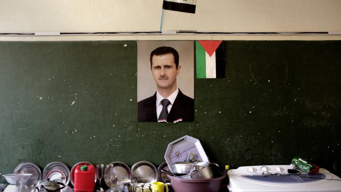 Da Jan Pêt Khorto var barn, blev han i skolen opdraget til at elske Hafez al-Assad, som blandt andet var afbildet på hans stilehæfte. Traditionen fortsatte med sønnen, Bashar al-Assad, hvis portræt her hænger i en skole i Damaskus i 2013.