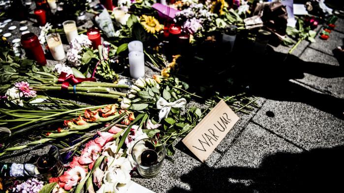 'Hvorfor?' står der på tysk på et skilt, der sammen med blomster og lys ligger foran indkøbscentret Olympia i München, hvor en angivelig højreradikal 18-årig mand fredag sidste uge dræbte ni mennesker.