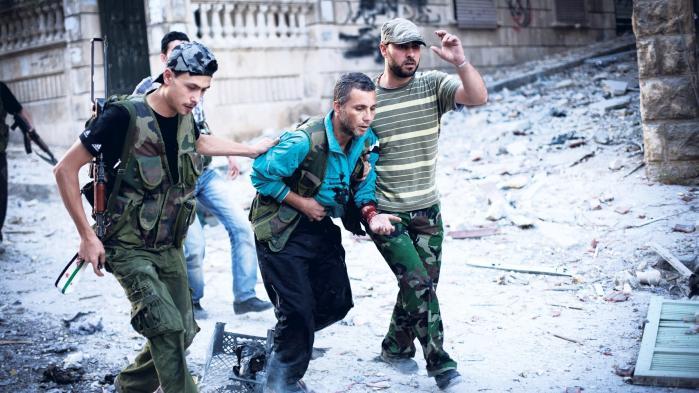 Vesten har svigtet både før, under og efter den syriske revolution blev til en borgerkrig, mener Mustafa Ismail. Her hjælper frie syriske oprørere en mand, der er blevet såret af en snigskytte i Aleppo.