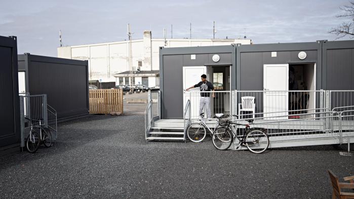 Flygtningene bor i 24 sorte containere beliggende rundt om et lille, stenbelagt område på størrelse med en stor parcelhusgrund. Halvejen hedder området. Boligpavillonerne er Dragørs løsning på et problem, der har ført til lokalpolitiske gnidninger flere steder i landet: Hvad skal kommunerne stille op med de flygtninge, man ikke kan finde permanent bolig til?