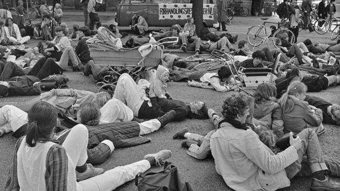 Gruppen 'Nej til Atomvåben i Norden' demonstrerer foran USA's ambassade i København i 1982. Demonstranterne ligger på gaden for at forestille lig dræbt af atombomber.
