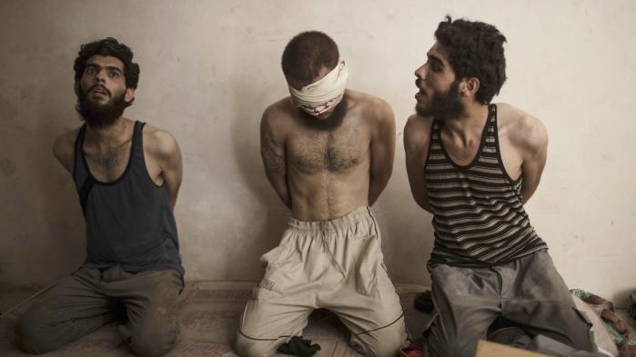En IS-kriger tilbageholdt af irakiske styrker i Mosul. De to andre mænd blev løsladt. Tilstedeværelsen af terrorgrupper som IS og al-Qaeda sker ofte med de mellemøstlige regimers stiltiende accept. så længe de ikke udfordrer regimerne.