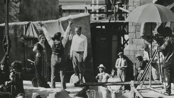 Teatermaler, scenograf og teaterinstruktør Svend Gade står midt i settet til stumfilmen 'Rosita' (1923), mens instruktør Ernst Lubitsch gestikulerer.
