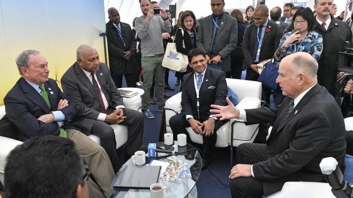 Tidligere New York-borgmester Michael Bloomberg (tv.) og Californiens guvernør, Jerry Brown (th.), er blandt de bærende kræfter i bevægelsem 'We Are Still In', som er i opposition til Donald Trumps klimapolitik. Her ses de to i samtale med COP-præsident Frank Bainimarama (nr. to fra venstre), der til daglig er ministerpræsident i Fiji.