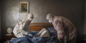 Frivillige fra Røde Kors iBergamo, Italien,tilser en kvindepå 88 år, som de formoder har COVID-19. For lidt over en måned siden, registrerede Italien sit første coronadødsfald. Fredag var 9.134 døde.