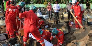 Indonesiske arbejdere sænker en kiste med et coronadødsoffer ned i jorden. Indonesiens hurtigtvoksende gravpladser er et tydeligt billede på, hvor mange mennesker, der på kort tid har mistet livet.